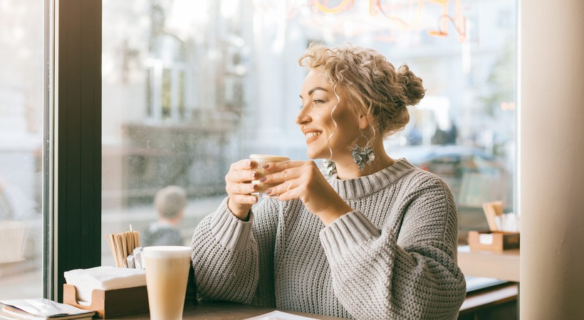 woman holding coffee with two hands